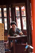 A Chinese man enjoys tea in the Huxinting Teahouse in Yu Yuan Gardens Shanghai, China