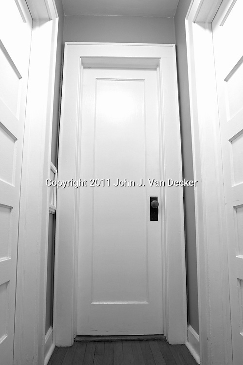 An closed door ahead in black and white. Image is of the Photographer's home.