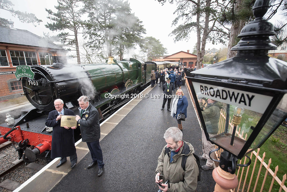 Broadway Station, Broadway, Worcestershire, UK. 30th March 2018.  A steam train carry members of the public departed from Broadway Station in the Cotswolds for the first time in almost 60 years today. On Good Friday, Lord Richard Faulkner of Worcester formally opened the station and traveled on the footplate of Great Western Railway-designed engine no.7903 'Foremarke Hall', the first public train to Cheltenham for 58 years. The new station has been built by GWSR volunteers to a similar design as the 1903 original station. Most of the stations on the former Stratford-upon-Avon to Cheltenham line were closed by British Railways in 1960 and the railway closed completely in 1976, with track and infrastructure removed by 1979. Pictured: Lord Richard Faulkner (standing left holding plaque) stands in front of the engine. // Lee Thomas, Tel. 07784142973. Email: leepthomas@gmail.com  www.leept.co.uk (0000635435)