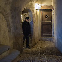 A man in the covered narrow cobbled passages in Santa Maria Del Monte in Varese, Italy