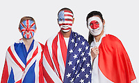 Portrait of young patriotic men with national flags and face painting smiling against white background