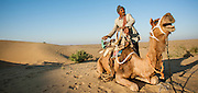 Desert man with camel on sand dunes (India)