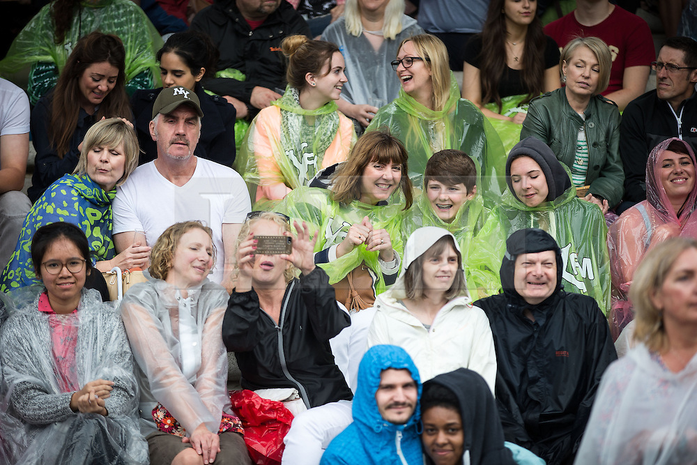 """© Licensed to London News Pictures . 02/07/2015 . Manchester , UK . Crowds wearing ponchos in the rain at the Castlefield Bowl at the opening of """" Summer in the City """" festival in Manchester. Photo credit : Joel Goodman/LNP"""