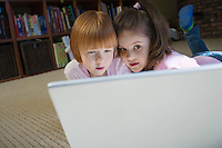 Young girls (5-6) lying on floor using laptop contemplating