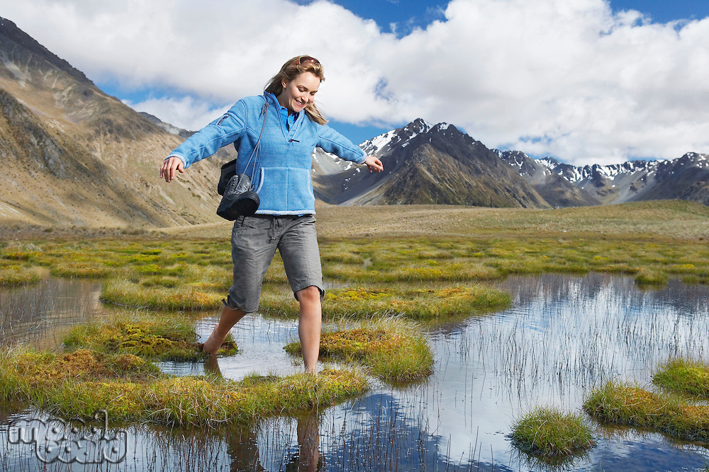 Woman walking barefoot through pond by mountains