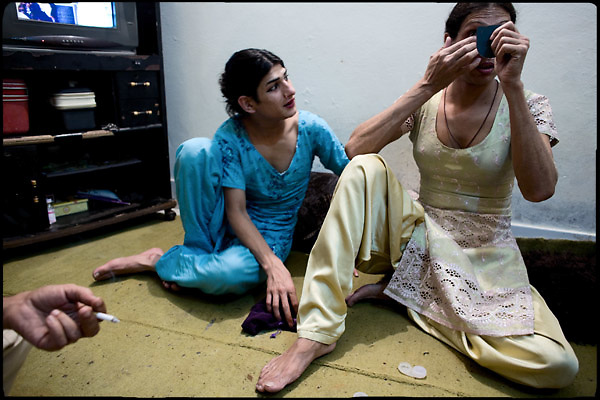 "Kastouri (left side),  a young transvestite of 16 years, looks up to his Guru Chabbo (on the right), 32 years old, transvestite by the youth. Transvestites people have created a community, a kind of an hierarchical staircase, based on rules handed down by generations.  Evening in Lahore, Pakistan on Monday, December 01 2008.....""Not men nor women"". Just Hijira, Kusra. Painted lips, Kajal surrounding their eyes and colourful veils..Pakistan is today considered a strongly, foundamentalist as well, islamic country. But under its reputation, above all over the talebans' continuos advancing, stirs a completely extraneous world, a multiethnic mixed society. Transvestites make part of it, despite this would not be admitted by a strict law. Third gender, the Hijira are born as men (often ermaphrodites) or with an ambiguous genital situation, and they have their testicles and penis removed through a - often brutal - surgical operation. The peculiarity is that this operation does not contemplate the reconstruction of a female organ. This is the reason why they are not considered as men nor women, just Hijira. They are often discriminated, persecuted  and taxed with being men prostitutes in the muslim areas. The members of this chast perform dances during celebrations, especially during weddings, since it is anciently believed that an EUNUCO's dance and kiss in the wedding day brings good luck to the couple's fertility...To protect the identities of the recorded subjects names and specific .places are fictionals."