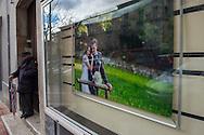 Sala Consilina, 10/02/2015: anziano con ombrello e immagine di matrimonio nella vetrina di un negozio di fotografia