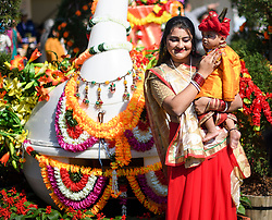 © Licensed to London News Pictures. 02/09/2018. Aldenham, UK. A woman poses with her son dressed as Krishna, next to a floral display at Bhaktivedanta Manor Temple in Aldenham, Hertfordshire during the Janmashtami Hindu festival. Janmashtami is an annual Hindu festival that celebrates the birth of Krishna. Bhaktivedanta Manor, the venue fo the event, was donated to the Hare Krishna movement in February 1973 by former Beatle George Harrison. Photo credit: Ben Cawthra/LNP