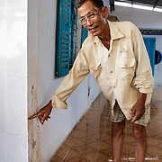 CAPTION: Mai Van Cho stands outside his house and points out how high the water rose in a previous flood. LOCATION: An Binh Ward, Can Tho, Vietnam. INDIVIDUAL(S) PHOTOGRAPHED: Mai Can Cho.