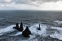 Reynisdrangar, basalt sea stacks situated under the mountain Reynisfjall near the village Vík í Mýrdal, southern Iceland..A Legend says that the stacks originated when two trolls dragged a three-masted ship to land unsuccessfully and when daylight broke they became needles of rock.