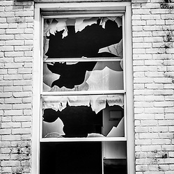 Photo of a broken window at the abandoned Glencoe-Auburn Buildings in Cincinnati Ohio. The Glencoe-Auburn Hotel and Glencoe-Auburn Place Row Houses was built in the late 1800's and is listed on the U.S. National Register of Historic Places. The complex is currently abandoned and in extremely poor condition.