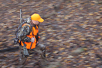 DEER HUNTER WEARING REALTREE AP CAMOUFLAGE AND BLAZE ORANGE WLKING THROUGH THE WOODS WHILE CARRYING A THOMPSON CENTER OMEGA MUZZLELOADER