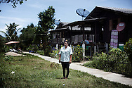 A Moken youth chooses to find work away from the sea, posing here in her 7-11 uniform outside her house in the Ban Tung Wa Moken village in Khao Lak, southern Thailand. The village is home to some 70 Moken families.