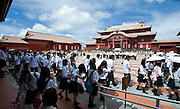 Schoolchildren wit to have their photo taken in front of the main Seiden hall inside the grounds of Shuri-jo Castle in Naha, Okinawa Prefecture, Japan, on June 24, 2012. Seiden functioned as the central structure of the Ryukyu kingdom for over 500 years and was restored in 1992. Photographer: Robert Gilhooly