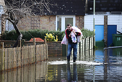© Licensed to London News Pictures. 25/02/2014. Basingstoke, Hampshire, UK. A man making his way through flood water with bagged possessions on Grampian Way in the Buckskin area of Basingstoke, Hampshire. Groundwater levels are continuing to rise slowly in the area, where many homes have been evacuated. Water is still being pumped by tankers, and taken to nearby sewerage plants. Photo credit : Rob Arnold/LNP