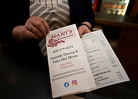 Manager Andrea Weeks holds a menu for patrons as the restaurant prepares to open outside dining options on Monday at Hart's Turkey Farm.   (Karen Bobotas/for the Laconia Daily Sun)