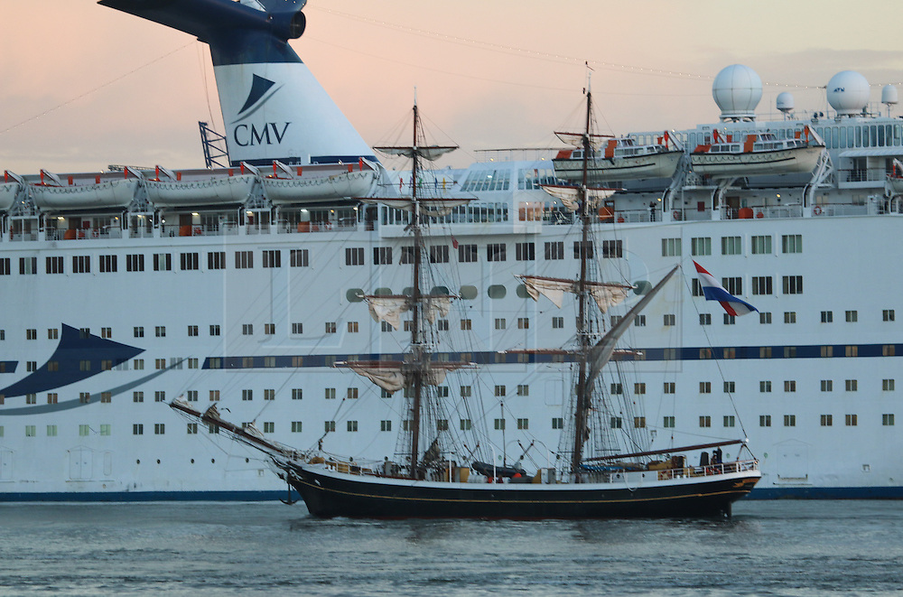 © Licensed to London News Pictures. 12/09/2016. A tall ship sails up the Thames at sunrise, passing a cruise ship at Tilbury, as seen from Gravesend. Gravesend recorded the hottest temperature of anywhere in the country in August. The south east is expected to have days of warm, sunny weather. Credit : Rob Powell/LNP
