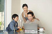 Father working on computer at dining room table wife and son watching