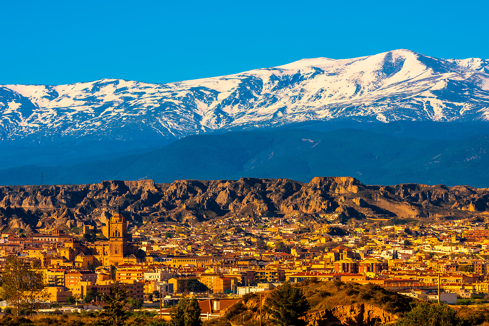 The town of Guadix, is where desert rock formations meet the snowcapped peaks of the Sierra Nevada Mountains,  Granada Province, Andalusia, Spain.