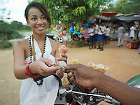 Young woman paying for ice cream at street market smiling