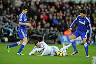 Gylfi Sigurdsson of Swansea falls under a challenge from Cesc Fabregas of Chelsea. Barclays Premier League match, Swansea city v Chelsea at the Liberty Stadium in Swansea, South Wales on Saturday 17th Jan 2015.<br /> pic by Andrew Orchard, Andrew Orchard sports photography.