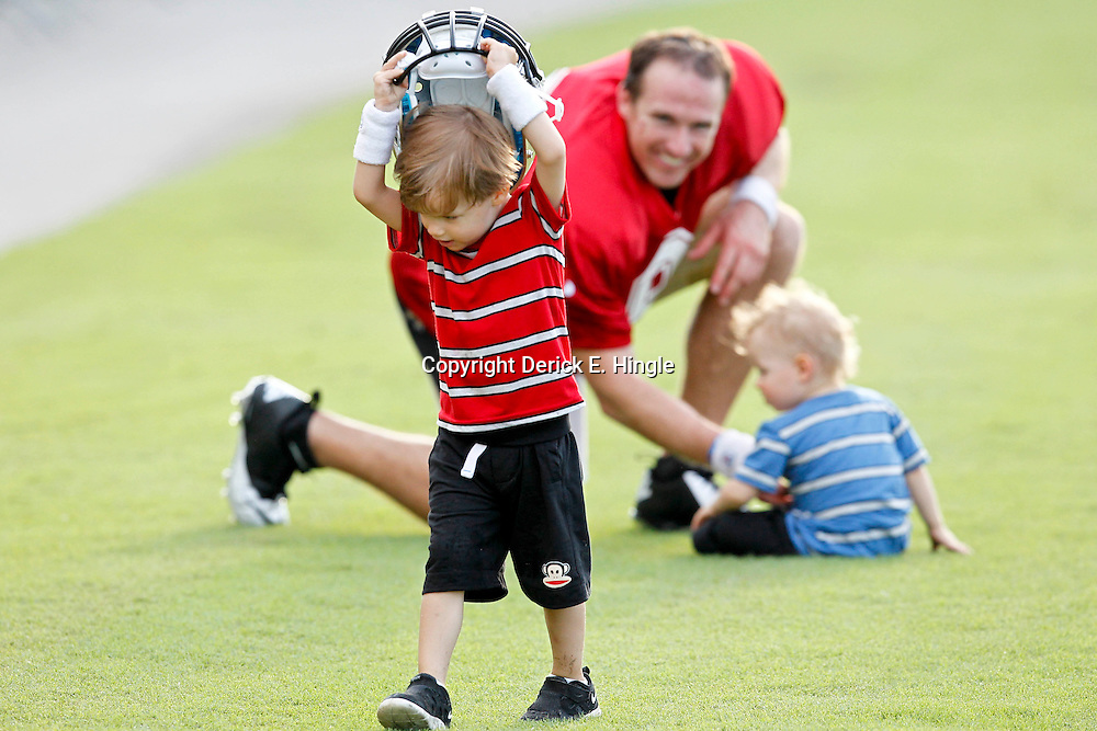 July 28, 2012; Metairie, LA, USA; Baylen Brees son of New Orleans Saints quarterback Drew Brees takes off with his helmet as Brees watches and plays with his youngest son Bowen following a training camp practice at the team's practice facility. Mandatory Credit: Derick E. Hingle-USA TODAY SPORTS