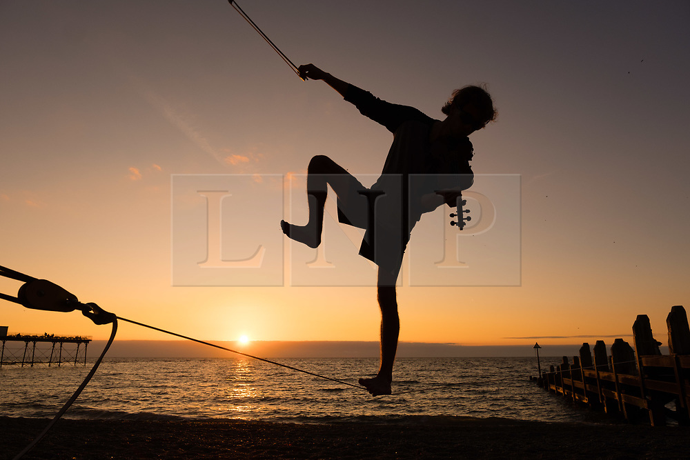 © Licensed to London News Pictures. 01/09/2017. Aberystwyth, Wales, UK. 21 year old postgraduate student ALEX FREEMAN, takes a break from his physics master's degree studies to play the violin and balance on slack-lines as the sun sets over Cardigan Bay on Aberystwyth, at the end of a bright and sunny first day of September .Photo credit: Keith Morris/LNP