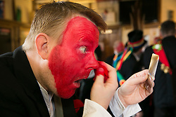"© Licensed to London News Pictures.10/1/2015.Sharnford, Leicestershire, UK. The annual plough tour by the Hinckley Bullockers took place today.Pictured, Steve Robinson adds the red dye to his face, the tradition stems from when farmers marked their sheep to stop them being stolen. Visiting seven venues around Leicestershire the Bullockers, some with with red painted faces, are seen pulling their decorated plough along the street before stopping to perform traditional dances.<br /> <br /> HISTORY -  On the first Monday after Twelfth Night - Plough Monday - the plough was prepared for the new season, dressed in gaudy ribbons and taken in procession around the villages. In South West Leicestershire the men pulling the plough, who ""raddled"" their faces, were known as Plough Bullocks and were aided and abetted by dancers who danced dances peculiar to the Eastern Counties. The Plough Bullocks and the Molly Dancers were last seen in this area at the turn of the century in Sapcote.<br />  Traditionally, the Plough Bullockers would stop at public houses, farms and large houses, dance and/or sing and demand recognition in the form of cash donations or drink. If neither was forthcoming the offending landlord's drive was ploughed up. Photo credit : Dave Warren/LNP"