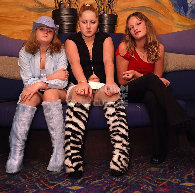 Three teenagers girls with fluffy boots sitting on a sofa, Cardiff, 2000's