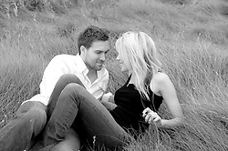 Young couple enjoying time together sitting in a field of grass