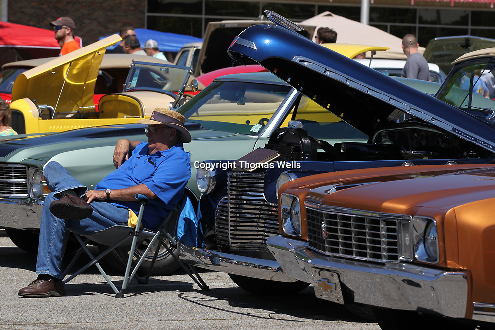 Harry Brown of Blue Springs makes himself comforable in front of his 1940 Chevy in order to answer any question vistors have have for him about the car at Saturday's Blue Suede Cruise.