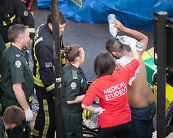 © Licensed to London News Pictures. 25/07/2017. London, UK. A victim of what is thought to have been an acid attack, has water poured on his head  - on the side of the road in Bethnal Green. Two men have been taken to hospital after flagging down police for help. Photo credit: Liam Creighton/LNP