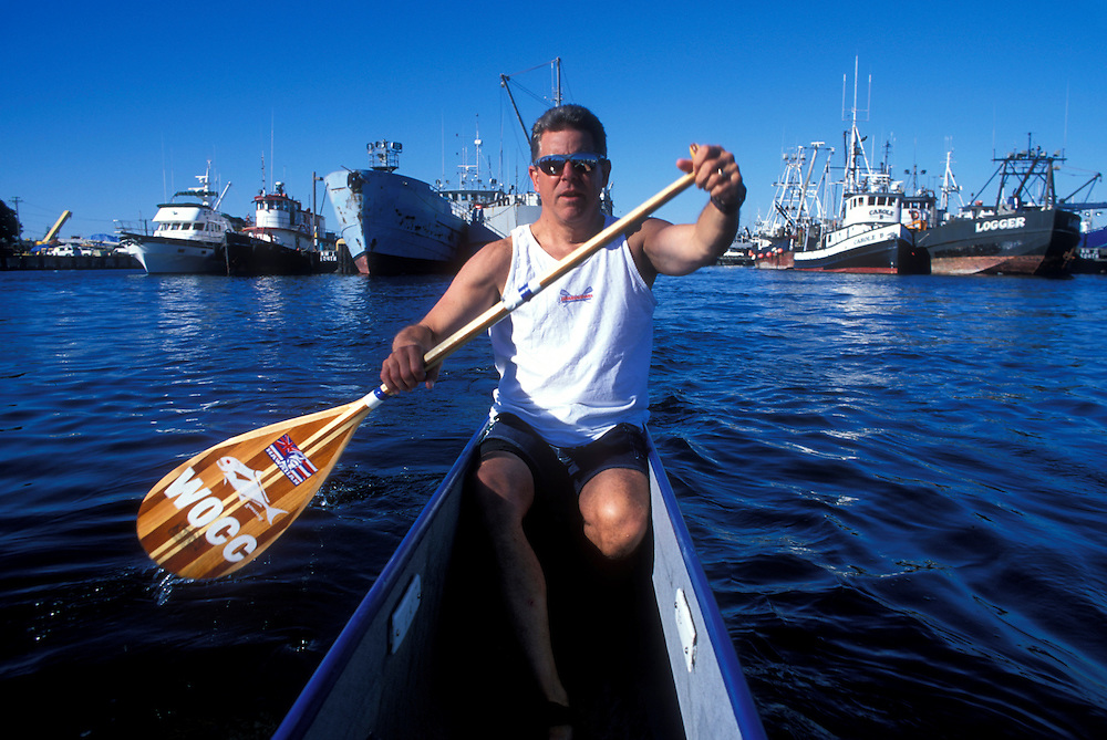 USA, Washington, Seattle, Steve Beaudry paddles outrigger canoe by fishing boats at Fisherman's Fall Festival in Ballard