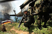 Members of the Jungla, a unit of the Colombian anti-narcotics police, jump onto a Blackhawk helicopter after destroying a drug lab in a coca field in the Colombian state of Bolivar, on July 3, 2007. (Photo/Scott Dalton)