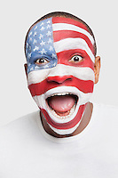 Portrait of surprised young man with North American flag painted on face shouting against white background