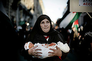 ROMA. UNA DONNA MANIFESTA CONTRO LA GUERRA IN PALESTINA CON IN BRACCIO UN PUPAZZO DI UN BAMBINO UCCISO, AVVOLTO IN UN LENZUOLO SPORCO DI SANGUE; ROME. A WOMEN DEMONSTRATED AGAINST THE WAR IN PALESTINE WITH A DOLL IN HER ARMS A CHILD KILLED, WRAPPED IN A SHEET STAINED WITH BLOOD