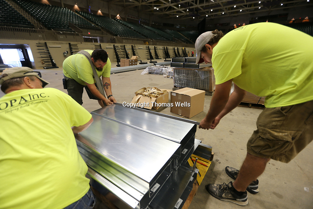 Chuck Morgan, from left, Tony Smith and Derek Glomski start applying the non-skid tape to the isle steps that will be installed later at the BancorpSouth Arena.