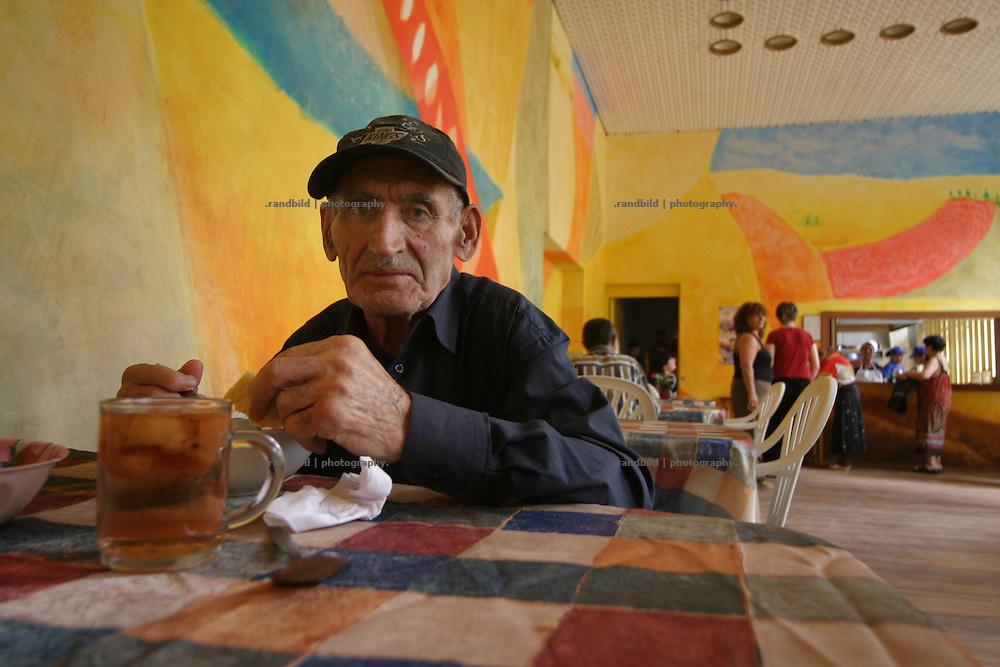 Ein Rentner sitzt alleine an einem Tisch in einer Armenküche in Tiflis, Georgien, und isst. - A pensioner is sitting alone at table for taking a meal in a poor peoples canteen in Tbilisi, Georgia.