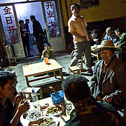 Rural migrants working on construction sites eat in a restaurant on the outskirts of a northeastern Chinese city.<br /> <br /> China is hoping by relocating farmers into cities they would start to buy food, making a break from the cycle of farmers consuming only what they produce.<br /> <br /> China is pushing ahead with a dramatic, history-making plan to move 100 million rural residents into towns and cities between 2014 and 2020 &mdash; but without a clear idea of how to pay for the gargantuan undertaking or whether the farmers involved want to move.<br /> <br /> Moving farmers to urban areas is touted as a way of changing China&rsquo;s economic structure, with growth based on domestic demand for products instead of exporting them. In theory, new urbanites mean vast new opportunities for construction firms, public transportation, utilities and appliance makers.