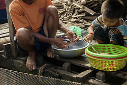 October 25, 2013 - Kompong Loung Commune (Kandal). A fisherman cuts tiny fishes that are used to make prohok, a popular local fermented fish paste.  © Thomas Cristofoletti / Ruom