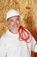 Portrait of smiling male construction worker with a red electrical wire