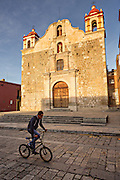 A bicyclist passes the Templo de la Preciosa Sangre de Cristo or Temple of the Blood of Christ in the historic district in Oaxaca, Mexico.
