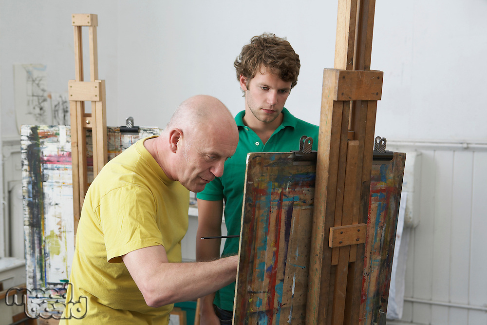 Student looking on as artist paints at easel in art studio