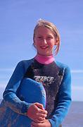 AJDM61 Girl in wet suit on beach against blue sky