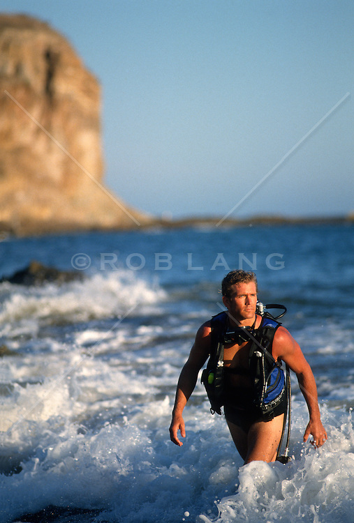 Male scuba diver walking out of the ocean in California