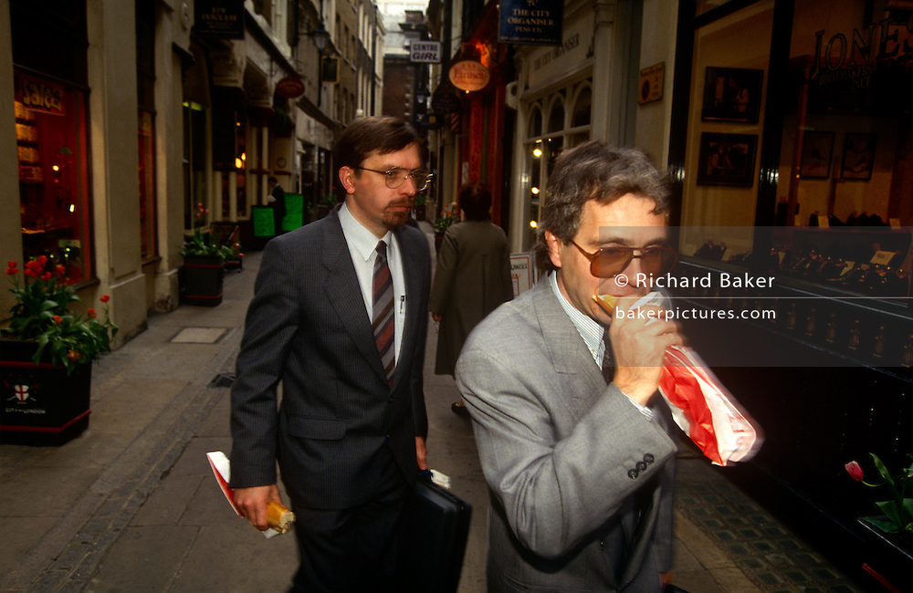 Office workers walk through a City of London street, the heart of the capital's financial district. It is lunchtime and two men have take-away sandwiches. One eats his on the go, biting into his long baguette from Pret a Manger in this narrow city street near St Paul's cathedral and the other chews his own.