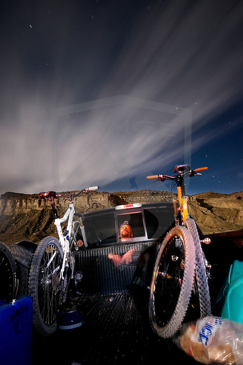 man in back of truck with mountain bikes in time lapse night photograph and streaking sky clouds and stars.  taken in the san rafael desert, green river, utah.