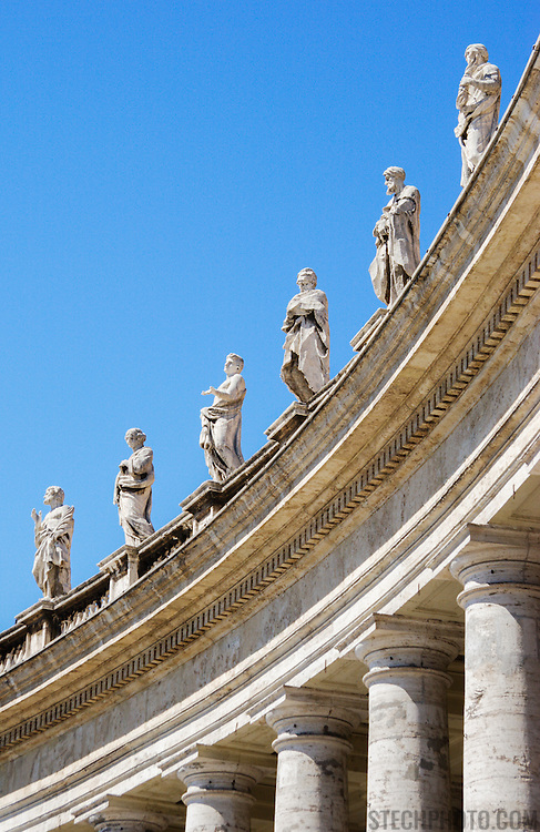 Statues mounted top of curved row of columns surrounding St. Peter's Square at the Vatican (Rome, Italy).