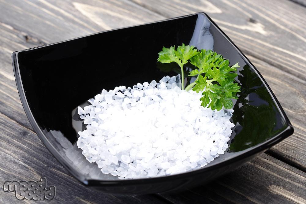 Salt in black bowl on wooden table