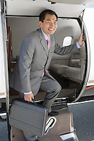 Asian businessman getting off airplane.